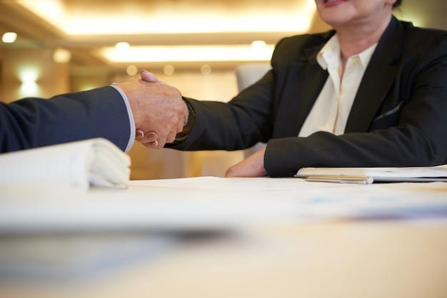 Handen van senior zakenpartners die de restauranttafel de hand schudden na een succesvolle vergadering