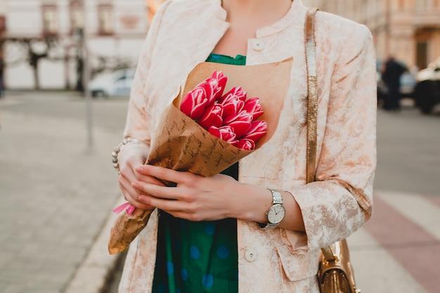 Handen van stijlvolle vrouw met bloemen boeket