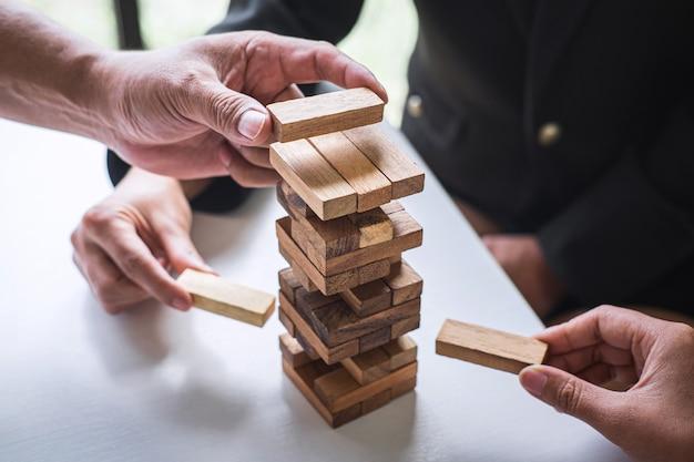 Handen van teamwerk coöperatief gokken die houten blok op de toren plaatsen om samen te werken