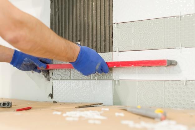 Handen van tegelzetter die keramische tegels installeren op de muur