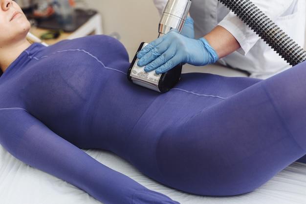 Handen van therapeut lipomassage tool te houden. schoonheidsspecialiste doet een mooi figuur voor een vrouw