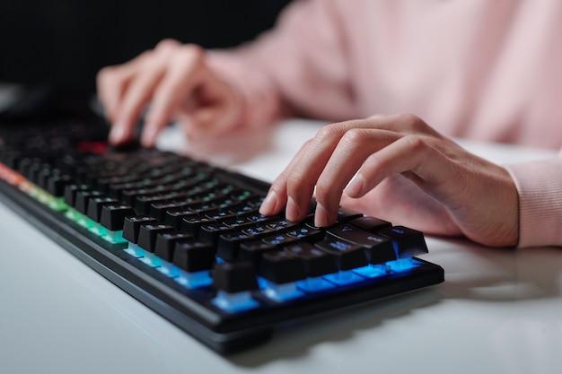 Handen van tiener over toetsen van computertoetsenbord te typen zittend door bureau en huiswerk