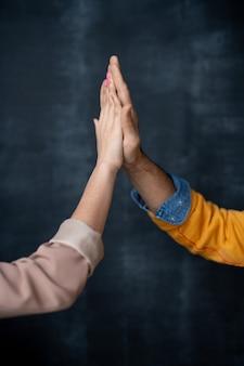 Handen van twee jonge succesvolle professionals in vrijetijdskleding die elkaar een high five geven terwijl ze elkaar begroeten