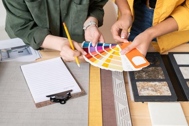 Handen van twee jonge vrouwelijke interieurontwerpers die overleggen over de kleurkeuze voor een van de kamers terwijl ze palet boven tafel houden