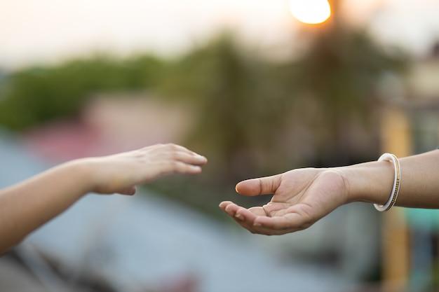 Handen van twee mensen die naar elkaar reiken