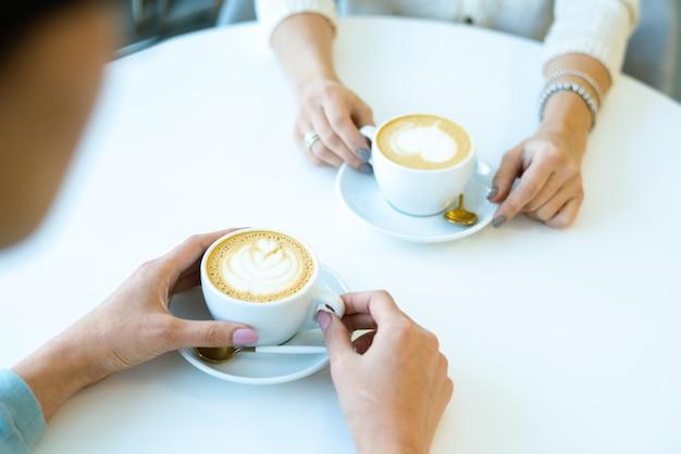 Handen van twee vriendelijke meisjes zitten aan tafel in café en hebben verse smakelijke cappuccino tijdens communicatie