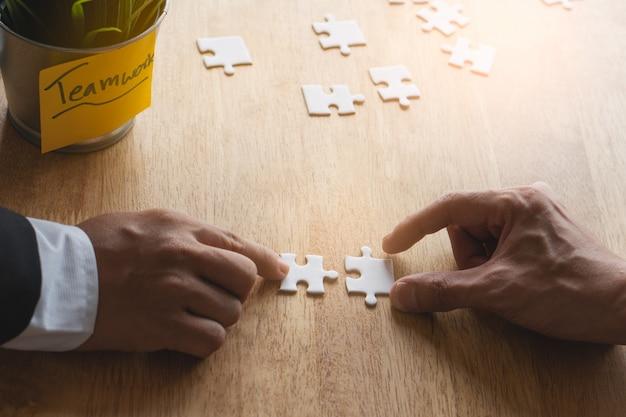 Handen van twee zakenlieden die puzzel op de werkende lijst samenvoegen.