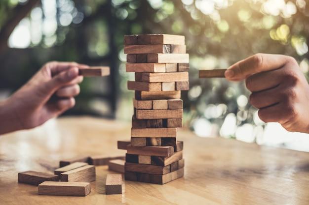Handen van uitvoerende samenwerking die houtblok op de toren plaatsen, gezamenlijk beheer