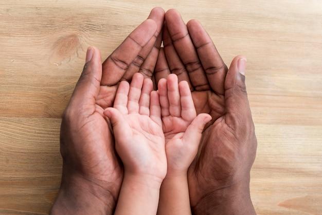 Handen van vader en kind op houten tafel