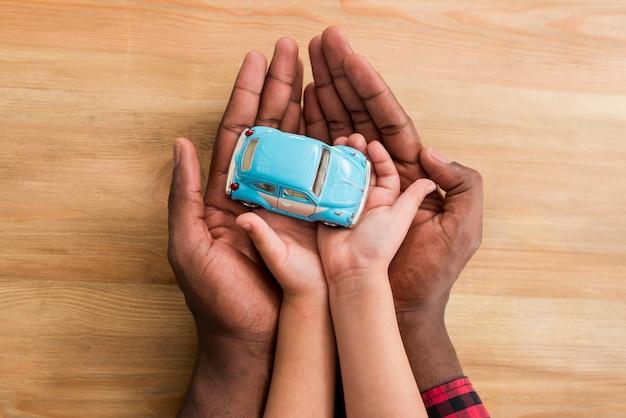 Handen van vader en kind speelgoedauto te houden