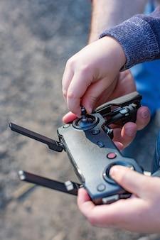 Handen van vader en zoon houden afstandsbediening joystick en loods quadrocopter