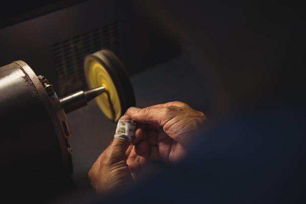 Handen van vakvrouw die aan een machine werkt