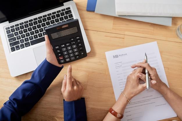 Handen van vastgoedmanager die aanbetaling op rekenmachine toont aan senior vrouw die bankdocument vult...