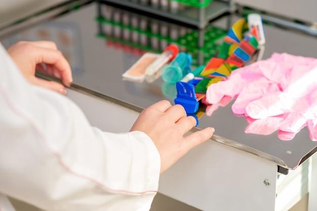 Handen van verpleegster bereidt zich voor op een bloedonderzoek in het laboratorium.