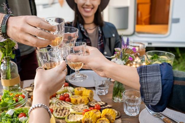 Handen van verschillende vrienden die met glazen wijn rammelen