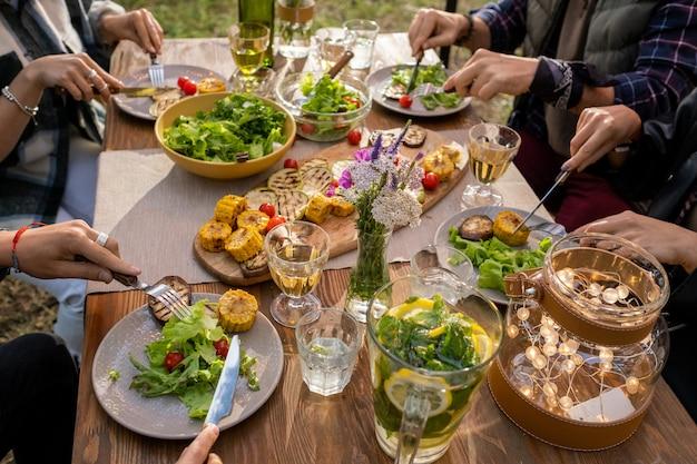 Handen van verschillende vrienden die met messen en vorken groenten eten