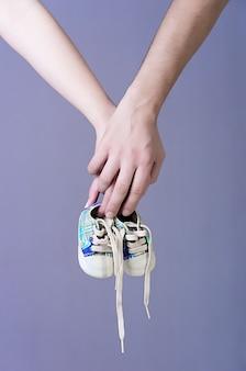 Handen van verwachtende ouders die een paar tennisschoenen van babyjongens houden