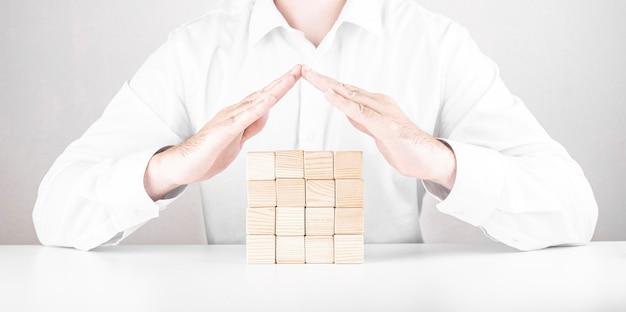 Handen van verzekeringsagent kleine huis opslaan gemaakt van houten
