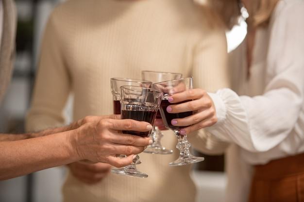 Handen van vier familieleden in vrijetijdskleding rammelend met glazen rode wijn tijdens het roosteren voor thanksgiving day tijdens het huisfeest