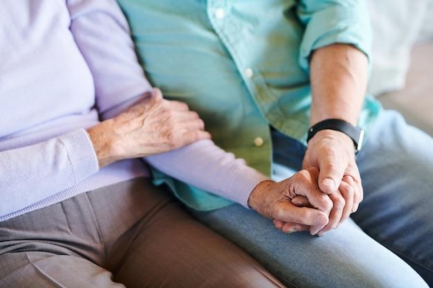 Handen van volwassen aanhankelijke echtgenoten in vrijetijdskleding tijd samen thuis doorbrengen en genieten van het samenzijn