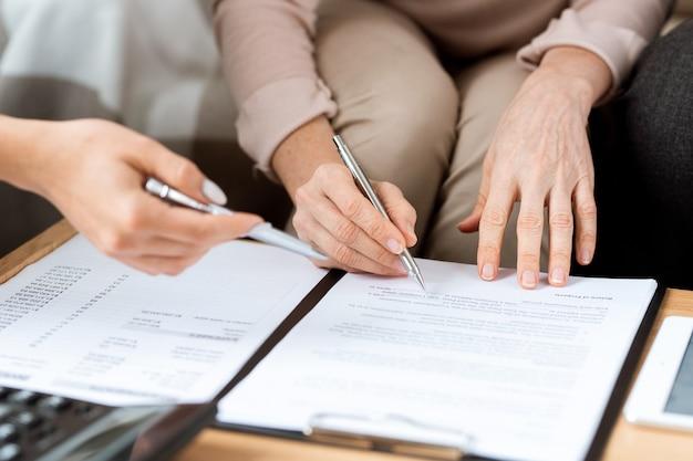 Handen van volwassen klant en makelaar in onroerend goed met pennen wijzen op contract voordat u het ondertekent