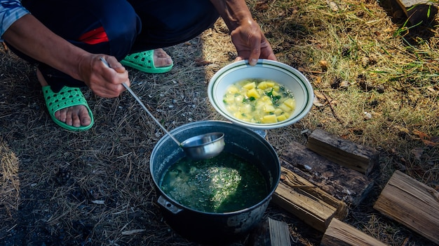 Handen van volwassen vrouw die soep uit een ketel gieten in een bord met pollepel. koken in de frisse lucht tijdens een wandeltocht. grote pot staande op het gras en brandhout. concept van toerisme.