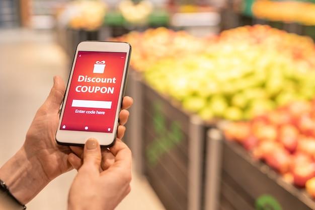 Handen van volwassen vrouwelijke consument smartphone met kortingsbon op het scherm op de muur van het display met fruit te houden