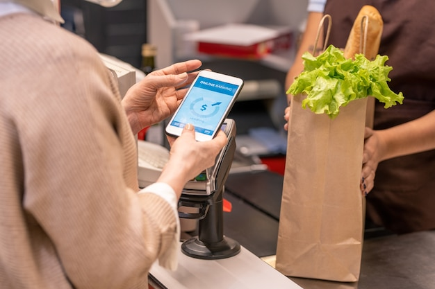 Handen van volwassen vrouwelijke koper met smartphone over betaalautomaat gaan betalen voor voedselproducten in supermarkt door kassa