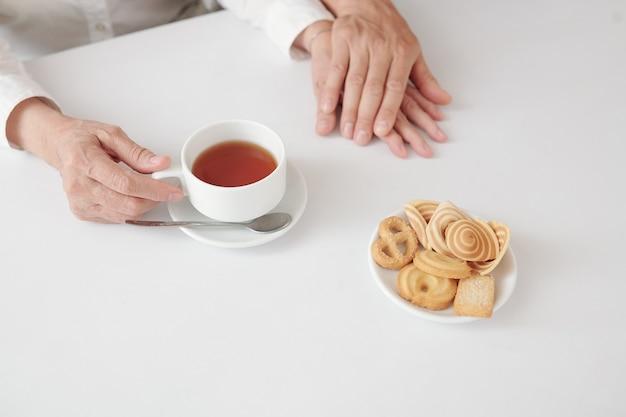Handen van volwassen zoon die de hand van zijn volwassen vrouw aanraakt wanneer ze thuis thee drinken met koekjes