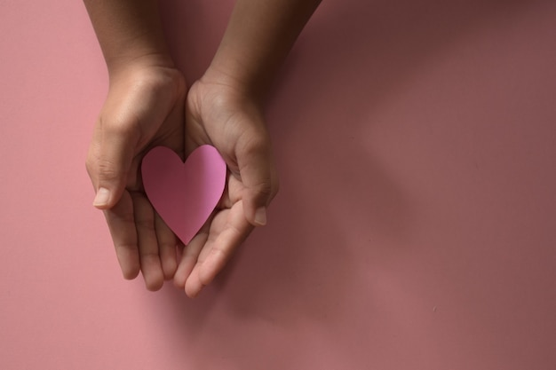 Handen van volwassenen en kinderen die een roze hart op een roze achtergrond houden, houden van een gezinsverzekering voor de gezondheidszorg