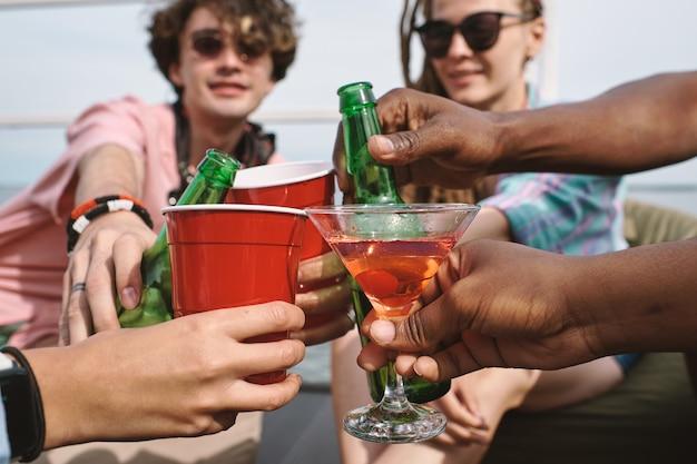 Handen van vrienden die roosteren met bierflessen, plastic bekers en martini-glazen op feestje