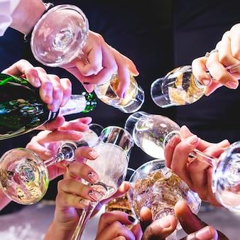 Handen van vrienden met wijnglazen