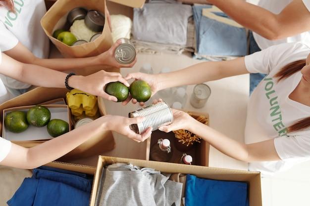 Handen van vrijwilligers die ingeblikt voedsel en groene citrusvruchten doorgeven bij het inpakken van dozen voor vluchtelingen