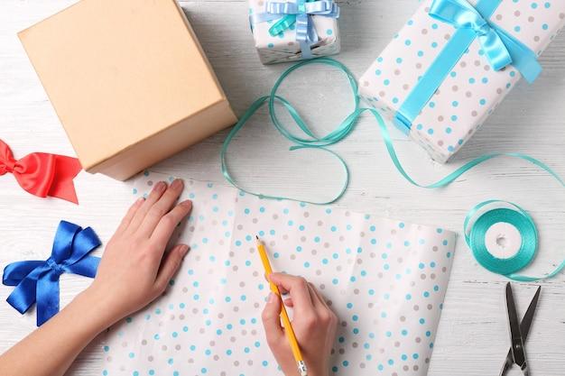 Handen van vrouw die cadeautjes inpakt voor vakantie