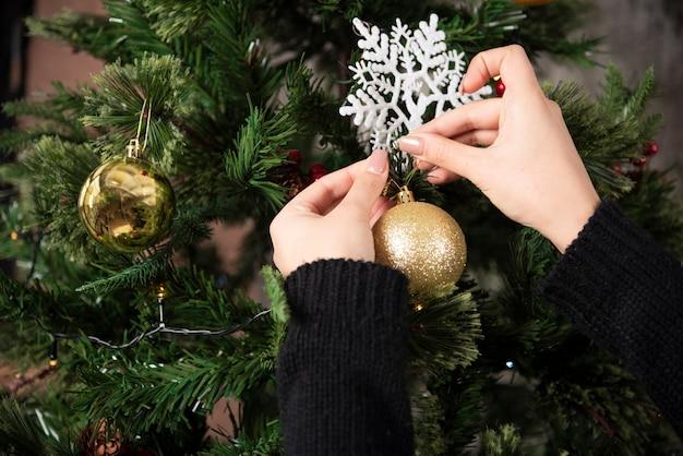Handen van vrouw die een kerstbal op een kerstboom hangen. hoge kwaliteit foto