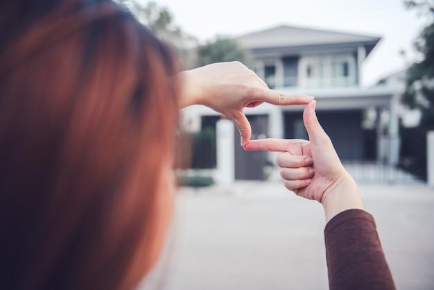 Handen van vrouw die kadergebaar met huis maken. planning voor het toekomstige bewonersconcept.