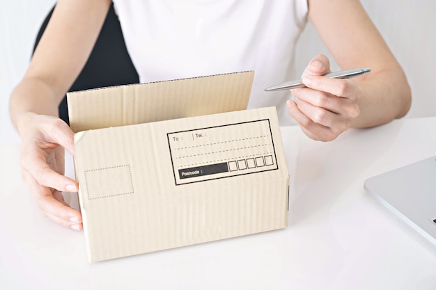 Handen van vrouw die op kartondoos bij lijst schrijven, die thuis concept werken
