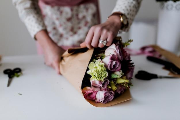 Handen van vrouw inwikkeling bos op papier