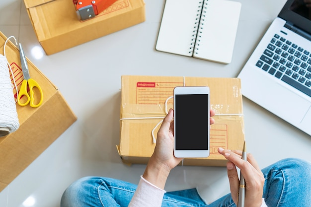 Handen van vrouw ondernemer met smartphone. business, technologie concept. bovenaanzicht, kopieer ruimte