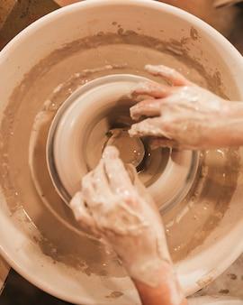 Handen van vrouw tijdens het maken van kleikom op aardewerkwiel