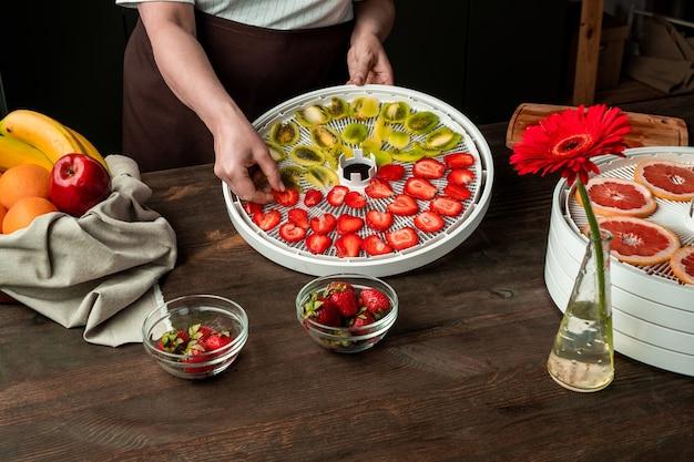 Handen van vrouw van middelbare leeftijd gesneden aardbeien en kiwi zetten dienblad van fruit droger onder verse bananen, sinaasappels, enz. op keukentafel