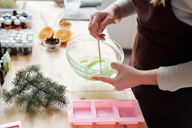 Handen van vrouw vloeibare zeepmassa mengen met groene kleur in glaswerk over roze siliconen mallen