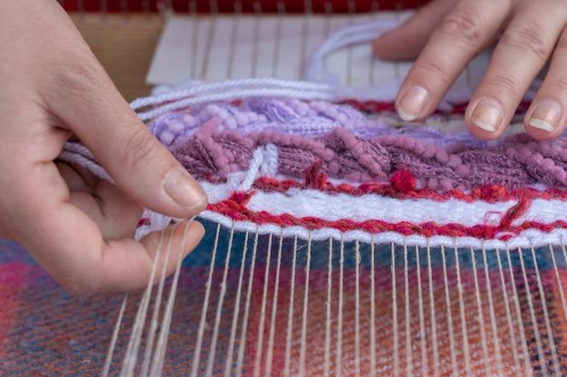 Handen van vrouw weven kleurenpatroon op traditionele hand weven houten weefgetouw, oekraïne. detailopname