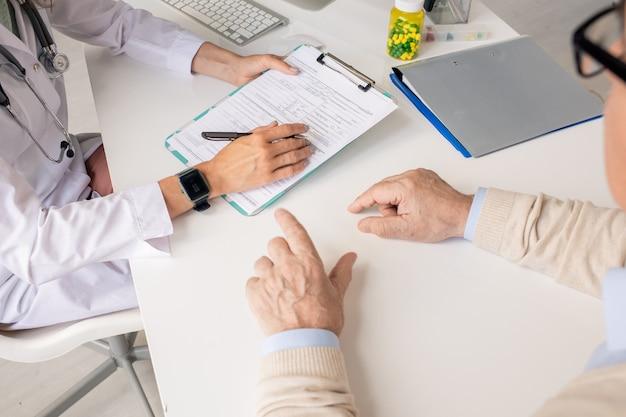 Handen van vrouwelijke arts met pen over medisch document in klembord en die van senior patiënt die dichtbij zit en iets uitlegt