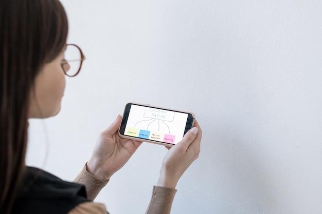 Handen van vrouwelijke bedrijfscoach die smartphone met stroomschema voor besluitvorming houdt terwijl hij door whiteboard staat