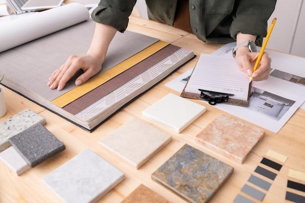 Handen van vrouwelijke interieurontwerper met potlood over papier maken van aantekeningen over kleur, patroon en textuur van wallpapers voor nieuwe klant