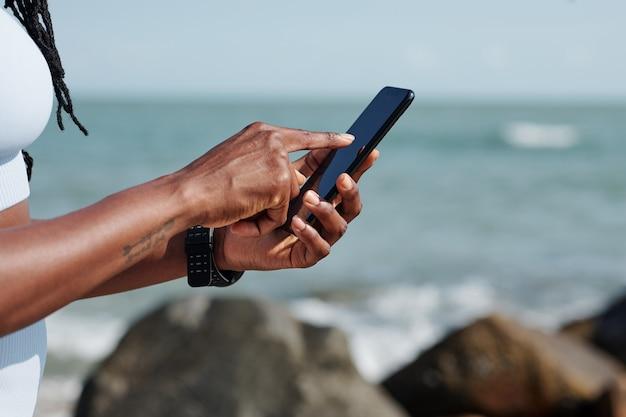 Handen van vrouwelijke jogger die fitnessapplicatie op smartphone installeert om haar activiteit tijdens de training te regelen