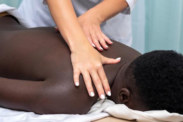 Handen van vrouwelijke masseuse die massage van schoudergebied doet aan zwarte man