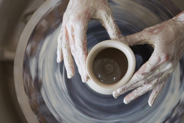 Handen van vrouwelijke pottenbakker die kleischip op spinnewiel beeldhouwen