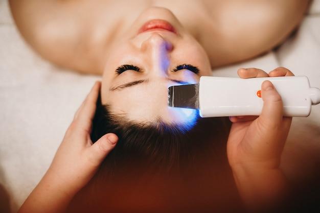 Handen van vrouwelijke schoonheidsspecialist doen een echografie mooie vrouwelijke gezicht reinigen.